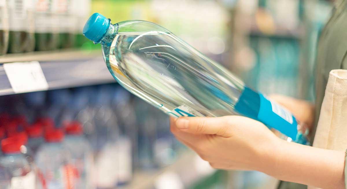Il controllo dell'etichetta di una bottiglia d'acqua
