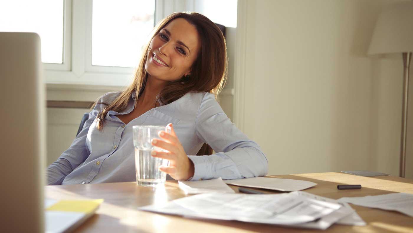 Impiegata che beve acqua in ufficio e sorride