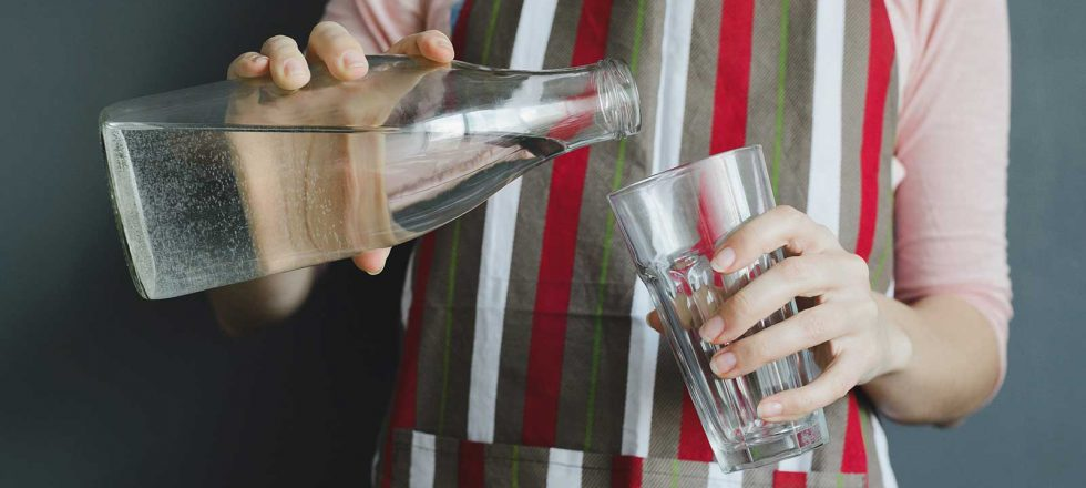 Donna che versa acqua da bottiglia di vetro